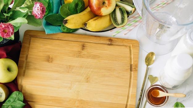 Plano de fundo vegan várias frutas e liquidificador em torno de tábua de madeira de corte