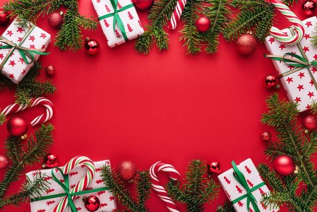 Plano de fundo vermelho de natal e ano novo. quadro decorativo de galhos de pinheiro, presentes, bolas de natal e bastão de doces. copie o espaço para o natal arrepiado