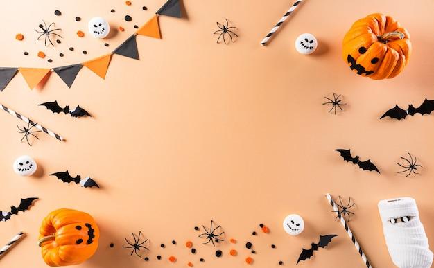 Plano de halloween com decorações feitas de abóbora, morcegos de papel e aranha negra