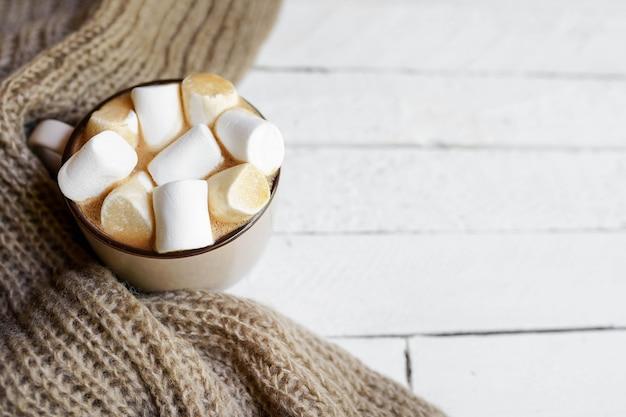 Plano de inverno deitado com lenço quente quadriculado, xícara quente de cacau no fundo branco de madeira com espaço para cópia.