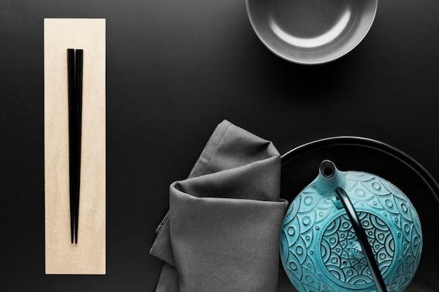 Plano de louça com pauzinhos e bule de chá