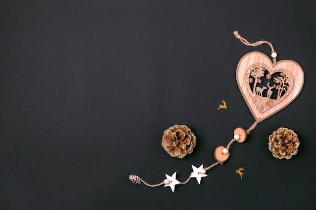 Plano de natal deitado com brinquedo de natal e pinhas em papel preto