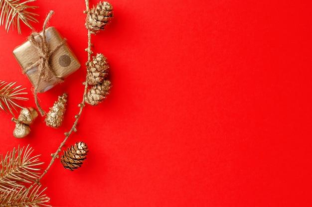 Plano de natal leigos composição no vermelho com ornamento dourado festivo no vermelho. cartão de felicitações vista superior,