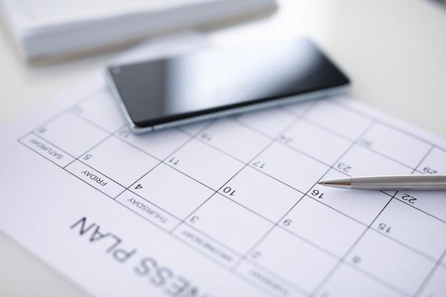 Plano de negócios com caneta e smartphone