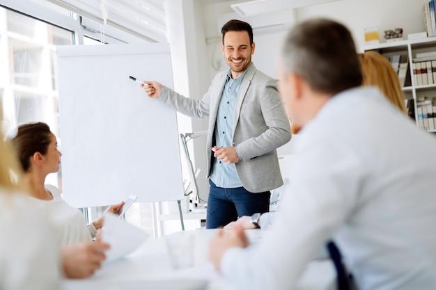 Plano de negócios explicado no flipchart pelo ceo aos funcionários