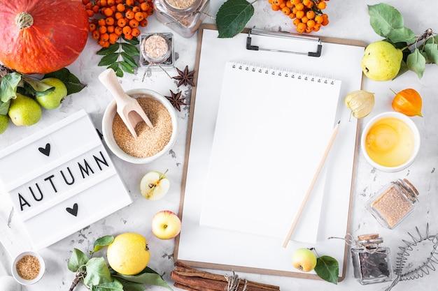 Plano de outono com mesa de luz com a frase outono. vista do topo. ingredientes alimentares para fazer torta de abóbora de outono em um fundo de pedra branca.