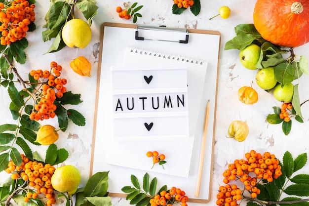 Plano de outono com mesa de luz com a frase outono.