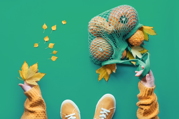 Plano de outono leigos no vibrante verde biscaia. abóboras laranja em saco de malha, folhas de bordo amarelas, mãos femininas no suéter laranja e um par de tênis de lona.