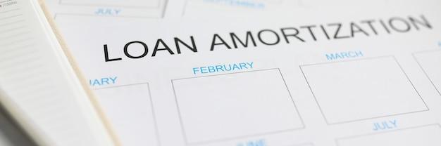 Plano de papel de amortização de empréstimo deitado na mesa de trabalho