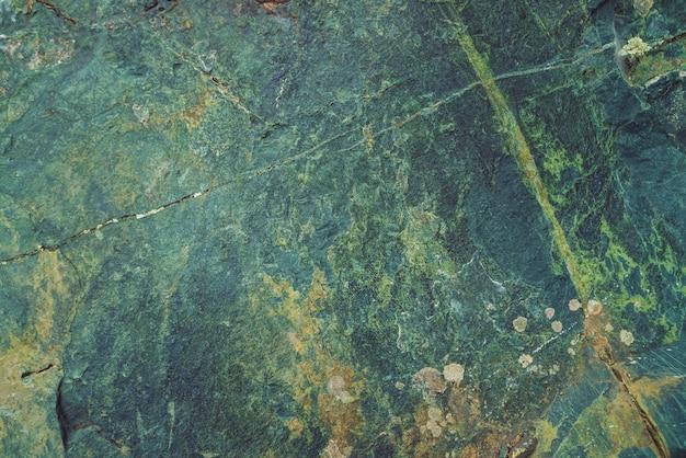 Plano de pedregulho multicolorido em macro. superfície bonita rocha close-up. pedra texturizada colorida. incrível detalhado de pedregulho das montanhas com musgos e líquenes. textura natural da montanha.