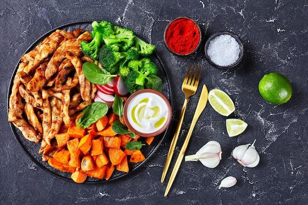 Plano de perda de peso: peito de frango grelhado e batata-doce assada, brócolis cozido em uma placa preta em um fundo de concreto escuro