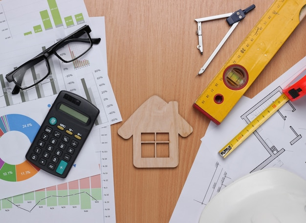 Plano de projeto arquitetônico, estatísticas e gráficos. ferramentas de engenharia e material de escritório na mesa, espaço de trabalho. conceito de construção de casa