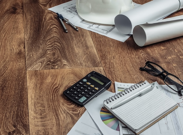 Plano de projeto arquitetônico, estatísticas e gráficos. ferramentas de engenharia e material de escritório no chão, espaço de trabalho. conceito de construção de casa