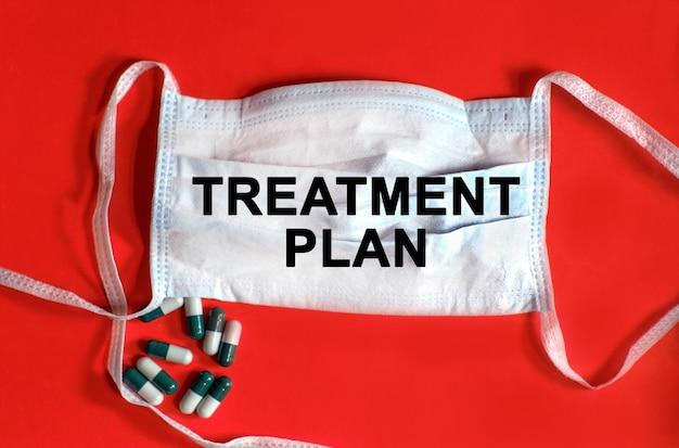 Plano de tratamento - texto em uma máscara protetora, comprimidos em um fundo vermelho