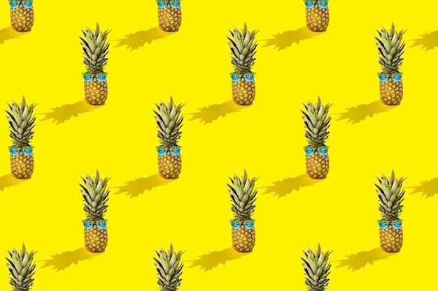 Plano de verão ensolarado mínimo plano de fundo de frutas. abacaxi fresco com óculos de sol com reflexo de palmas no padrão de fundo amarelo ensolarado.