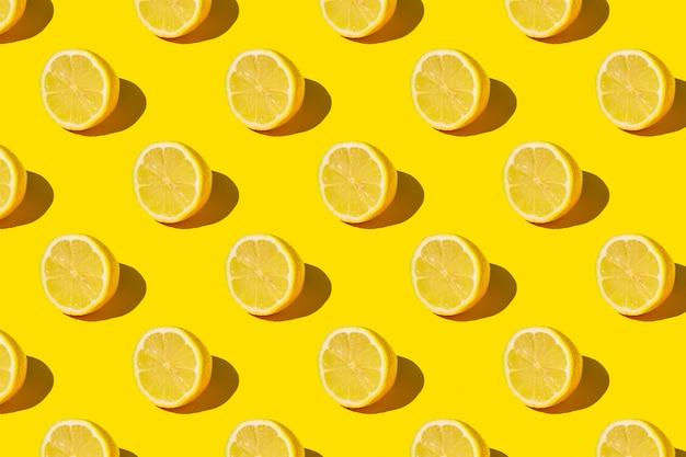 Plano de verão ensolarado mínimo plano de fundo de frutas. fatias de limão fresco no padrão de fundo amarelo.