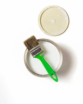 Plano deitado sobre um fundo branco, a vista de cima, um pincel verde e uma lata de ferro com tinta e uma tampa.