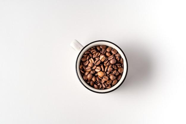 Plano deitar uma xícara de grãos de café isolados no fundo branco, copie o espaço para o texto.