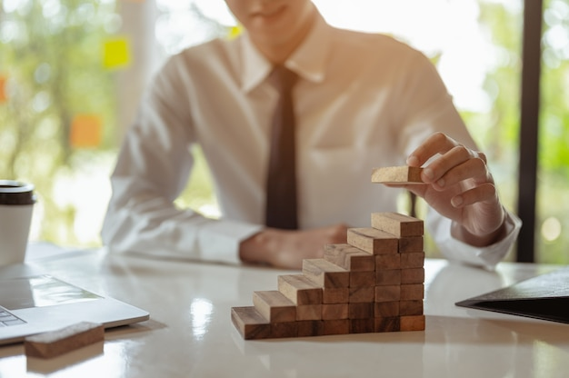 Plano e estratégia no conceito de risco empresarial, mão do homem empilhando e empilhando um bloco de madeira