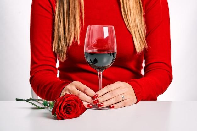 Plano fechado de uma mulher com um suéter vermelho, uma rosa e uma taça de vinho, isolado em um fundo branco. c conceito de casal e encontro.
