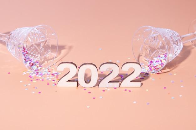 Plano festivo de ano novo com números 2022 e sombras duras com óculos e decoração brilhante