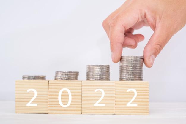 Plano financeiro para 2022. rk coloca moedas em pilhas em cubos de madeira, conceito de planejamento de orçamento.