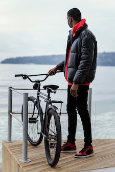 Plano geral de homem adulto e sua bicicleta