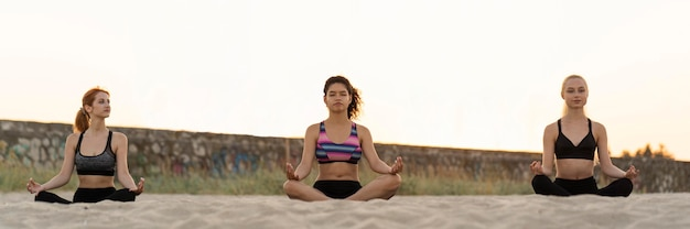 Plano geral de meninas meditando na praia