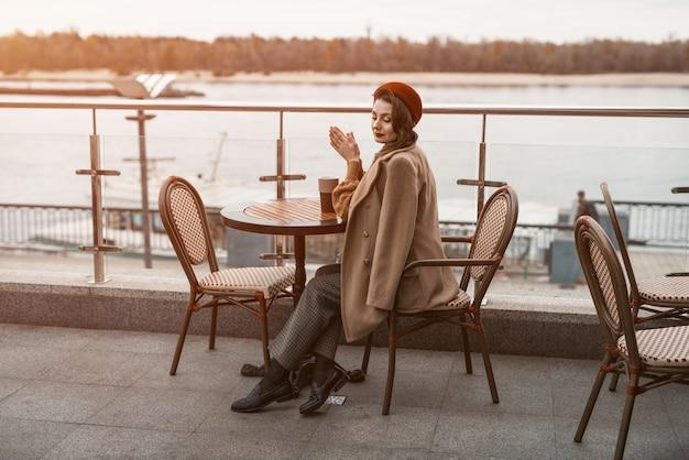 Plano geral de uma jovem parisiense atenciosa com uma caneca de café na mesa e uma boina vermelha