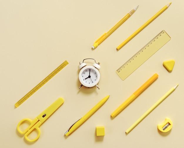 Plano horizontal com relógio e material escolar estacionário em amarelo