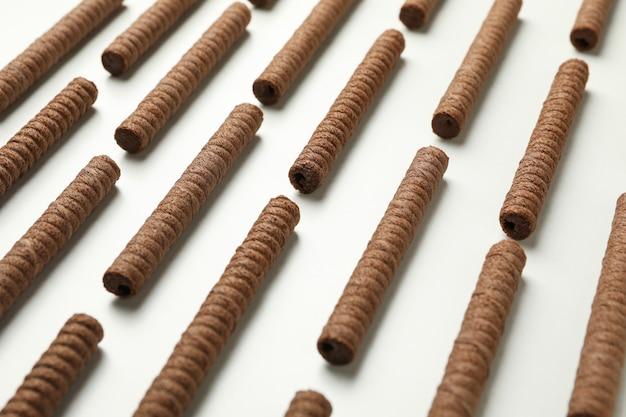 Plano horizontal com rolinhos de bolacha de chocolate em branco