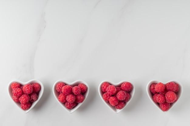 Plano horizontal com taças de framboesas em forma de coração na mesa de mármore copie o espaço frutas frescas deliciosas