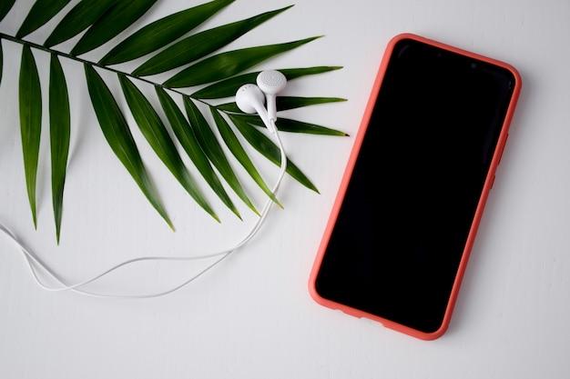 Plano horizontal com telefone celular, fones de ouvido e folha de palmeira