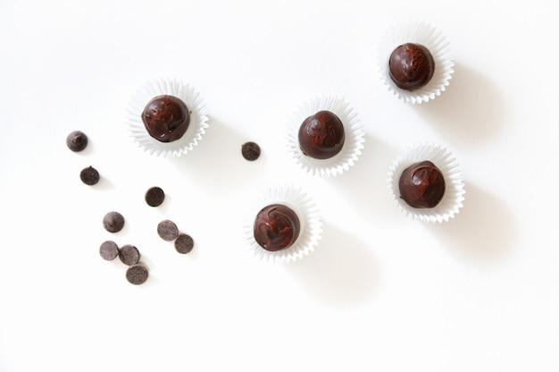 Plano horizontal com trufas de chocolate polvilhadas com morangos liofilizados em embalagens de papel e comprimidos de chocolate espalhados na superfície branca