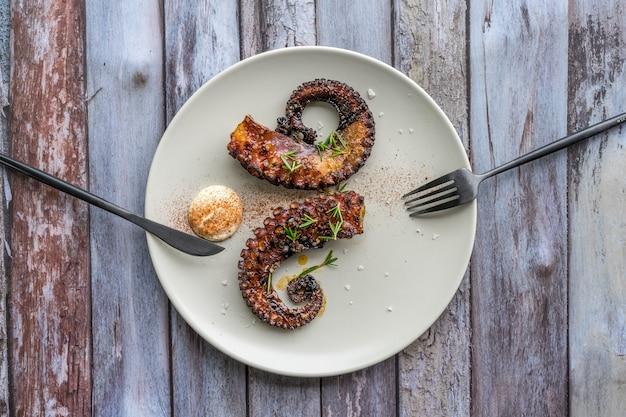 Plano horizontal de um prato com os braços de polvo com especiarias em um prato branco e com talheres
