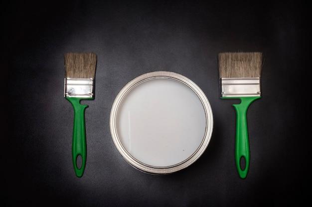 Plano horizontal, dois pincéis verdes e pratos com tinta, em um fundo preto texturizado com uma vinheta.