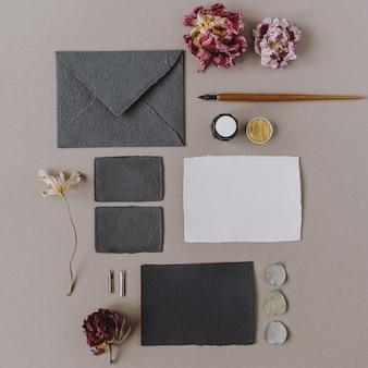 Plano leigo cartão de papel em branco vazio, envelope, caneta, botões de flores em bege. camada plana, vista superior