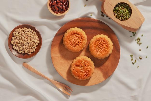 Plano leigo conceitual de mooncake de comida mid-autumn festival. texto no bolo significa felicidade.