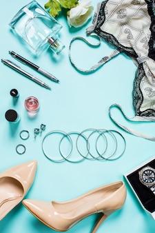 Plano leigo, vista superior, simulação de roupas sexy femininas e acessórios em um fundo turquesa. sapatos, pulseira, perfume