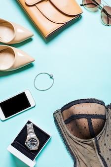 Plano leigo, vista superior, simulação de roupas sexy femininas e acessórios em um fundo turquesa. telefone, óculos de sol, pulseira
