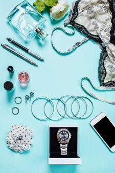 Plano leigo, vista superior, simulação de roupas sexy femininas e acessórios em um fundo turquesa. telefone, pulseira, perfume