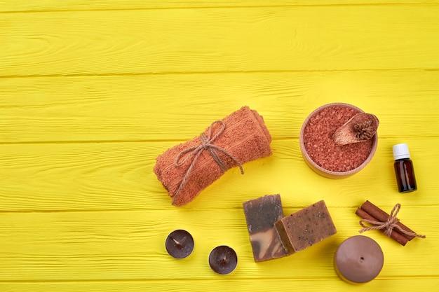 Plano leigos coisas marrons na mesa de madeira amarela. toalha enrolada com sal e velas.