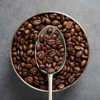 Plano leigos grãos de café na colher e tigela