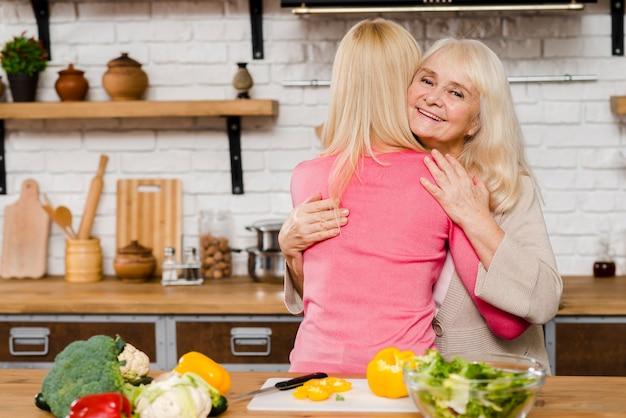 Plano médio da mãe abraçando a filha