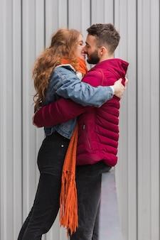 Plano médio de casal romântico abraçando