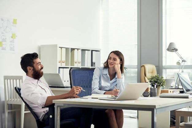 Plano médio de dois colegas de trabalho sentado na mesa e conversando
