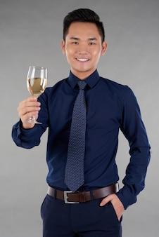 Plano médio de homem alegre brindando com um copo de vinho branco