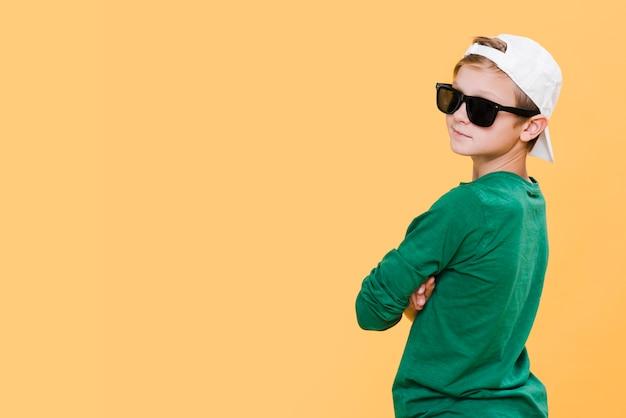 Plano médio de menino com óculos de sol e cópia espaço