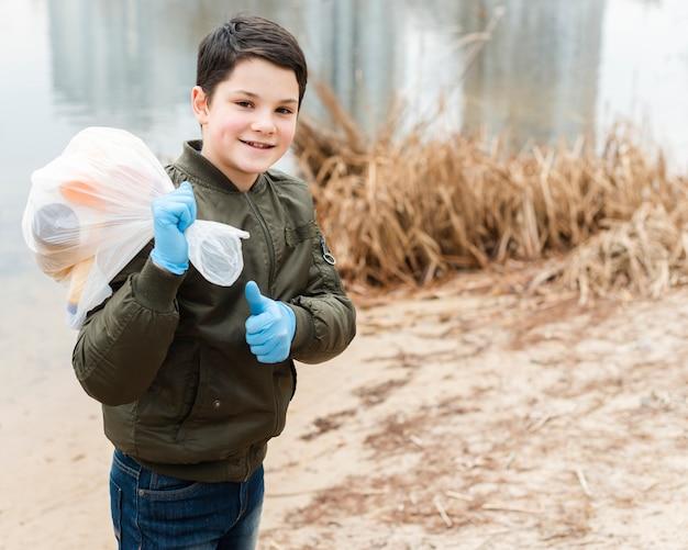 Plano médio de menino com saco de plástico