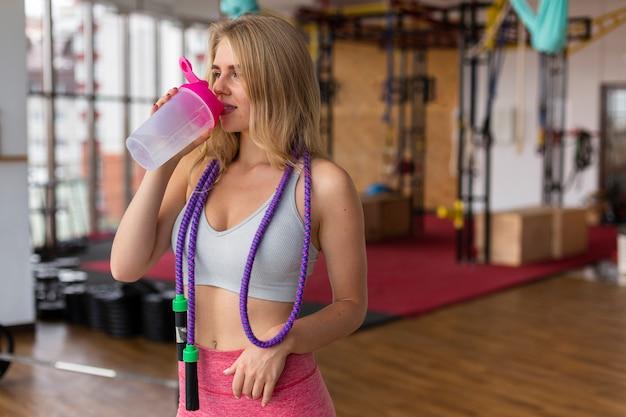 Plano médio de mulher bebendo água